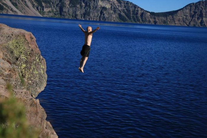 Noah Church jumping into Crater Lake