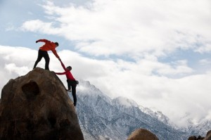 Person helping another climb a mountain